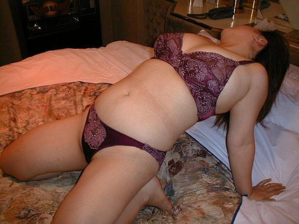 ベッドの上で下着姿の熟女